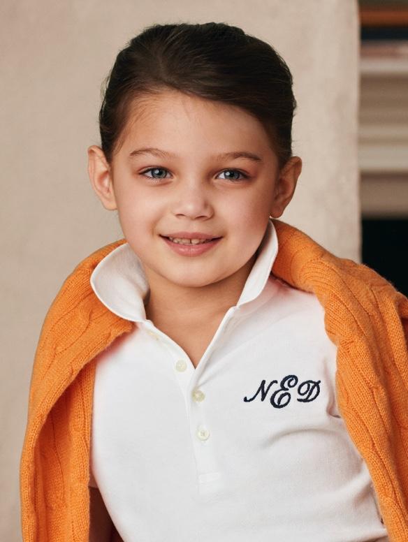 CYOカスタムの白のポロシャツを着て方にオレンジのケーブルニットをかけた男の子