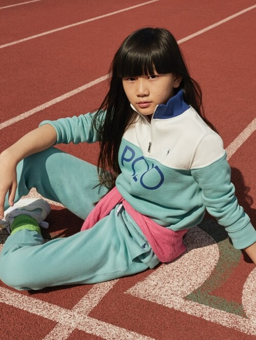 陸上のトラックの上に座った、ターコイズ色のPolo Sportのスウェットを着た女の子